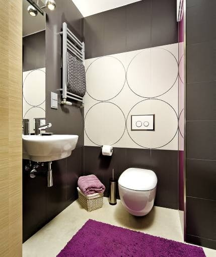 Na okrągło. W tej łazience ścianka sięga do sufitu. Wykorzystano ją do celów dekoracyjnych - została w całości wyłożona płytkami. Jasne kafle ułożono w taki sposób, by ozdobne geometryczne motywy utworzyły duże okręgi. Celowym zabiegiem aranżacyjnym jest też wybór umywalki i podwieszanego sedesu w zaokrąglonych kształtach.