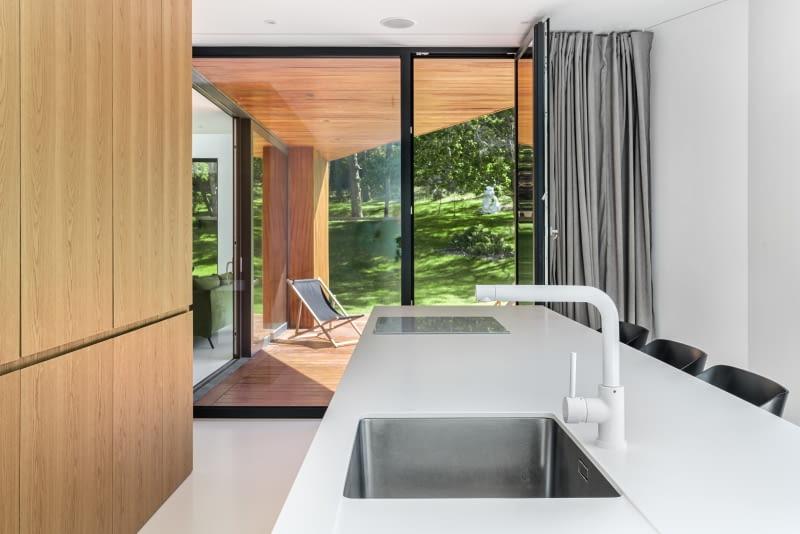 Прямоугольная кухня представляет собой длинный островок, соединенный с барной стойкой, и ряд мебели из светлого дерева, скрывающий необходимые удобства - все это почти буквально окружено садовой зеленью, льющейся через большое остекление.