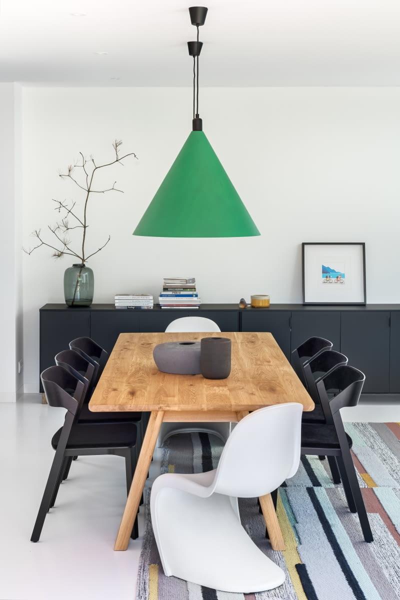 Столовая в гостиной - это пространство, где встречаются люди, мебель, формы и материалы, все на белом полимерном полу, частично покрытом старинным школьным ковром.