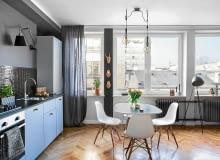 NEUTRALNE SZAFKI (z IKEA, uchwyty zamieniono na gałki z H&M Home) nabrały charakteru po wykończeniu ściany czarną mozaiką (Leroy Merlin). Wyżej - miedziany zegar DIY marki Ilva (cyfry i wskazówki przykleja się do ściany). Kuchnię oświetla kinkiet z ruchomym ramieniem (dobrelampy.pl).