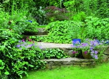 Kamienne murki wraz z posadzonymi na podwyższeniu roślinami tworzą ekran osłaniający ogród.