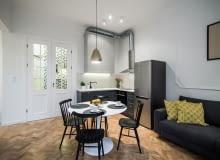 Ozdobami salonu są krzesła w stylu vintage i wisząca pozłacana lampa