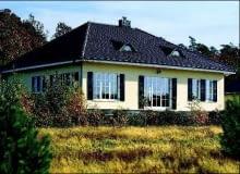 Domostwo na planie prostokąta nakryte czterospadowym dachem - zwarta bryła i dodatkowo okiennice ograniczają straty ciepła i ułatwiają ogrzewanie budynku. Poddasze zwiększa powierzchnię domu, ale skosy zmniejszają komfort życia na poddaszu