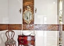 Urządzenia sanitarne w łazienkach stają się coraz mniej widoczne, zwykłe szafki są zastępowane przez komódki. Na plan pierwszy wysuwają się ozdobne wykończenia, dekoracje i dodatki. Bo teraz modne są wnętrza urządzone w wyrazistym stylu.<BR /><b>Inspirowana barokiem.</b> Pani domu bardzo lubi zakupy na pchlich targach, w poszukiwaniu oryginalnych przedmiotów serfuje po internecie. Na aukcji staroci w Szwecji kupiła piękną komódkę oraz lustro w dekoracyjnej ramie. Po krótkim namyśle postanowiła wykorzystać te nabytki w... łazience. Komodę przerobiono na szafkę pod umywalkę, a rama lustra z barokowymi zdobieniami w kształcie kwiatów i liści (podobnie jak uchwyty szafki) stała się motywem przewodnim w aranżacji całego wnętrza ? roślinny wzór można dostrzec również na brązowych płytkach. I tak mimo nowoczesnych elementów piękne stylowe przedmioty narzuciły wnętrzu pałacowy styl. <BR />WNĘTRZA - ŁAZIENKI. Mimo sentymentu do staroci gospodarze nie uciekają od nowoczesności. W podwieszonym suficie zamontowano głośniki połączone z centralnym systemem audio w mieszkaniu.