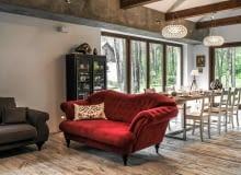 JADALNIA. Na granicy jadalni i części wypoczynkowej stoi reprezentacyjna pikowana kanapa. Żywy kolor mebla wybrano specjalnie, by przełamać wszechobecne brązy i szarości.