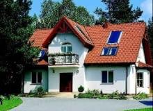 Parterowy budynek z użytkowym poddaszem, tradycyjnie wykończony jasnym tynkiem i dachówką to uniwersalny przepis na dom