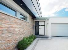 Wybierając skrzydła w jasnych kolorach, możemy optycznie 'schować' wejście do domu. Na zdjęciu: drzwi aluminiowe AT400, Ud = 0,75 W/m?K, wielopunktowe ryglowanie, ciepły próg, klasa RC2, cena 17 649 zł (netto), INTERNORM