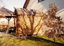 Mały skład na drewno wykorzystany jako parawan. Osłania letni taras i wnętrze ogrodu od strony dodatkowej bramy wjazdowej, stanowiącej 'wyłom' w żywopłocie.