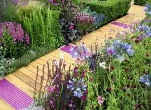 'Dekory' z ceramicznej mozaiki to dobry sposób na ożywienie drewnianej ścieżki. Do ich barwy warto dopasować odcienie kwiatów na rabatach