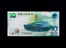 "BEIJING - JULY 08: The front of the new 10-yuan commemorative bank note on July 8, 2008 in Beijing, China. The People's Bank of China (PBOC), the country's central bank, will issue a commemorative bank note with a face value of 10 yuan ($1.46) on Tuesday to mark the Beijing Olympic Games. On one side is a picture of the National Stadium, known as the Bird's Nest, the main venue for the Olympic Games in August. The other side of the note has an illustration of the famous ancient Greek marble statue of a discus-thrower, Discobolus, portraits of athletes and the Arabic numeral ""2008"". The PBOC said it would issue a total of 6 million commemorative notes, which would be circulated in the currency market with the same denomination as the regular 10-yuan notes. (Photo by Feng Li/Getty Images)"