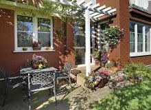 Aranżacje ogrodów. Mały ogród w kwiatach. Na ścianach, stoliku, schodkach - miejsce dla kwiatów znajdzie się wszędzie