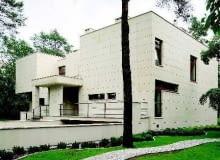 Elewacja domu. Płaski dach i prostopadłościenne bryły obłożone płytami piaskowca nadają współczesnej rezydencji oryginalny charakter