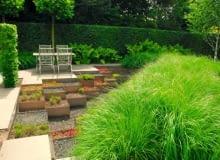 Sprytne rozwiązanie - ogród z 'samoobsługowych' sukulentów w aluminiowych skrzyniach i gigantyczej rabaty z trwałych ozdobnych traw.