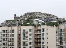 This Aug. 12, 2013 photo released by Chinas Xinhua News Agency shows a residential building with a rocky style villa on its roof, in Haidian District of Beijing, China. Beijing authorities are planning to demolish the bizarre rooftop villa embedded in rocks, trees and bushes that allegedly was built illegally atop a 26-story apartment block in the capital. (AP Photo/Xinhua, Luo Xiaoguang) NO SALES