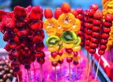 W Azji karmelizowane owoce są bardzo popularne. Sprzedaje się je na patyczkach niczym u nas lizaki. Natomiast wStanach Zjednoczonych na Halloween popularne są 'candy apples'.