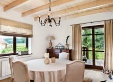 <B>Wnętrze zostało urządzone w rustykalnym stylu, dlatego pani domu udekorowała okna prosto drapowanymi zasłonami z lnianego płótna. Aranżacja jest równie naturalna i piękna jak Puszcza Knyszyńska widoczna na horyzoncie.</B> <BR />Długie zasłony w drzwiach balkonowych i rolety w oknie uszyto z grubego, gęsto tkanego lnu. Pani domu tak podoba się ten rodzaj tkaniny, że wybrała ją także na obicia krzeseł, obrus oraz abażur lampy.