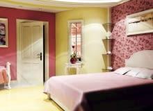 Projektowanie wnętrz. Projekt 1. W sypialni połączono elementy romantyczne (m.in. kwiecista tapeta, bibeloty) z nowoczesnymi (halogeny w podwieszanym suficie). W półokrągłej ściance zrobiono podzielone szprosami okienko z dekoracyjną ramą. Kwiat ustawiony na stylizowanej konsolce wydaje się z ciekawością zaglądać do łazienki.