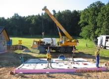 Budowa domu z prefabrykatów. Etap pierwszy - przygotowanie fundamentów. Już na tym etapie trzeba znać rozplanowanie urządzeń w łazienkach i kuchni domu, aby w podłodze na gruncie wyprowadzić instalacje w odpowiednie miejsca