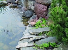 Płyty granitowe wystają nad taflę wody, aby folia na pionowym brzegu była niewidoczna.