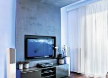 <B> Dawniej potrzebowały solidnej szafki, dziś lekkie i płaskie telewizory coraz częściej wieszamy na ścianie. Projektanci wnętrz proponują różne rozwiązania, dzięki którym miejsce do oglądania wygląda ładnie i jest wygodne. </B><BR /> TELEWIZORY: Projektant chciał, aby salon wyróżniał się z reszty mieszkania. Motywem przewodnim aranżacji stał się kształt litery C. Tworzą ją płyty gipsowo-kartonowe pokryte dekoracyjnym tynkiem imitującym beton, które zamontowano pod sufitem i na części ściany, oraz docięta na wymiar wykładzina dywanowa (podstawa C). Formę tej litery ma również stolik kawowy przy kanapie.