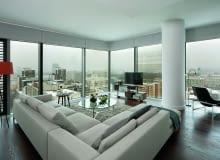 W tym salonie mebli nie warto dosuwać do ścian ze szkła, by nie tracić wspaniałego widoku za oknami.