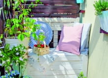 Oparcie balkonowej ławy zostało namalowane na drewnianym ekranie. Na pierwszym planie pomalowany na niebiesko wiekowy kociołek w roli donicy.