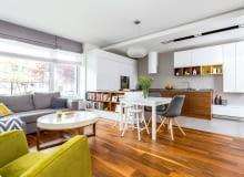 PÓŁWYSEP KUCHENNY od strony pokoju zmienia się w biblioteczkę. Nad stołem (IKEA) wisi oryginalna lampa Caboche (proj. Patricia Urquiola i Eliana Gerotto). Jest zbudowana z poliuretanowych kul, które zwielokrotniają światło.