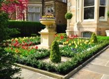 Wiosna w tym ogrodowym zakątku jest malownicza dzięki tulipanom. Kiedy przekwitną, zastąpią je niskie rośliny jednoroczne.
