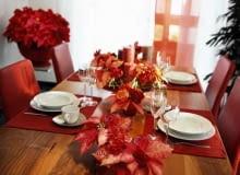 Nastrojowa dekoracja stołu. Poinsecje ułożono w niskich naczyniach z pojedynczymi goździkami i nerine.
