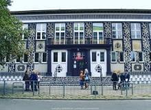 Dekoracja architektoniczna wykonana przez włoskiego artystę Opiemme na fasadzie jednej z łódzkich szkół. Mural reinterpretuje architekturę socrealizmu i czerpie z lokalnych tradycji