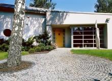Wejścia do domu strzeże dwumetrowy totem. Drewniane drzwi - poszerzone i podkreślone wnęką ładnie kontrastują z aluminowymi elementami wykończenia budynku.