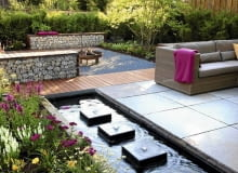 Small garden with wicker sofas on decked and paved patio, backed by Fargesia murielae - Bamboo hedge. Rectangular pond with row of square water features