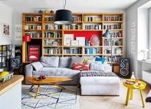 Stare i nowe wzornictwo w idealnej harmonii. Stolik o organicznej formie, lampa podłogowa z lat sześćdziesiątych XX wieku (ocalona z pobliskiego śmietnika) towarzyszą współczesnej kanapie i dywanowi z kolekcji IKEA Stockholm 2017. Żółty stolik Around i designerski koszyk na cytryny to przykłady nowoczesnego wzornictwa duńskiej marki Muuto (Scandinavian Living). Wykonana na zamówienie biblioteczka służy także jako miejsce eksponowania ceramiki oraz rysunków polskich ilustratorów: Agaty 'Endo' Nowickiej, Arobala i Agaty Bogackiej.