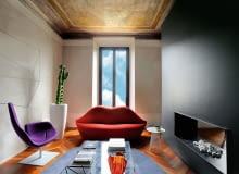 W rękach projektantów z ZetaStudio przestrzeń nabrała teatralnego charakteru. Czarna ściana tłumi światło, a jednocześnie wydobywa sufitowy fresk. Sofa Bocca (Gufram), projekt z lat 70., to hołd oddany przez turyńskie Studio 65 Salvadorowi Dalemu.