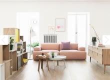 Przepis na to wnętrze? Białe ściany, kilka mebli w stylu vintage i duża, miękka sofa w kolorze rozbielonego różu