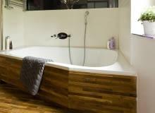 Łazienka, obudowy z drewna. Tekowy parkiet (cena od 209 zł/m kw.) na obudowie i na podłodze sprawia, że duża wanna wtapia się w tło.