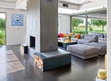 Wypoczynkowy obszar strefy dziennej wytycza dwustronny kominek - geometryczna forma zdelikatnie ryflowanego betonu. Szarą paletę wnętrza dopełnia obraz Marii Widelak.