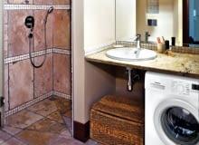 Wnętrza. Kamienny blat z umywalką służy również jako półka na kosmetyki. Inne rzeczy są trzymane w kuferku stojącym obok pralki. Wnętrze oświetla sufitowa lampa z trzema ruchomymi reflektorkami i kinkiety zamontowane na lustrze.