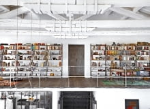 Biblioteka i gabinet na antresoli nad wejściem to najbardziej kolorowa część domu. Podłogę ułożono z desek różnych długości. Masywne belkowanie spięte klamrami podkreśla industrialny charakter wnętrza.
