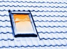 Okno dachowe. Zalegający zimą śnieg.