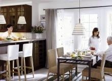Szereg stojących szafek kuchennych w wyraźny sposób oddziela strefę kuchni od salonu