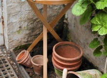 Wooden Table with Cut Flowers and Garden String with Terracotta Plant Pots and Geranium Foliage (Pelargonium)