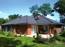 Taras ziemny wykonany z jasnych płyt kamiennych - kontrastuje z kolorem elewacji domu