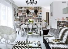 Wszechobecna biel: w tym kolorze są ściany, podłogi i większość mebli; właściciele przemalowali nawet pianino! Na takim neutralnym tle dobrze prezentuje się kolekcja książek, płyt i obrazów. Żyrandol, kupiony w jednym z marketów budowlanych, w innym wnętrzu mógłby wydać się pretensjonalny. Tu świetnie pasuje do stylizowanego stołu (IKEA) oraz srebrzystych krzeseł w stylu glamour. Głównym bohaterem salonu jest zrobiona na zamówienie biblioteczka. Boczne półki są ścięte, dzięki czemu tworzą spójną całość ze skośną ścianą.