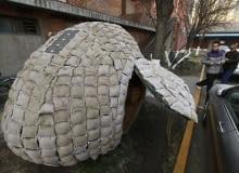 Visitors take photos of an egg-shaped mobile house near its owner Dai Haifei's office building in Beijing December 3, 2010. Dai, who is from central China's Hunan province and cannot afford Beijing's high rental prices, has been living in the house which costs about 6427 yuan ($965). The house is made of bamboo strips, steel bars, heat prevention and waterproof materials, sacks filled with fermented wood chips and grass seeds, as well as one solar-cell panel, local media reported. REUTERS/Petar Kujundzic (CHINA - Tags: BUSINESS SOCIETY)