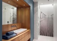 W łazience uwagę przykuwa czarno-białe zdjęcie orłowskiego molo, a także wnęka w wykończeniu z dębowej czeczoty, która pięknie kontrastuje z morską barwą meblowej zabudowy. To w niej chowają się kosmetyki, pralka, deska do prasowania i pozostałe przybory potrzebne do utrzymania porządku. Dzięki temu łazienka jest uporządkowana.