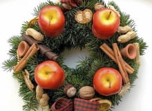 Ozdoby adwentowe. Wieniec ze świecami-jabłkami, laskami cynamonu, orzechami i drobnymi dekoracjami ceramicznymi