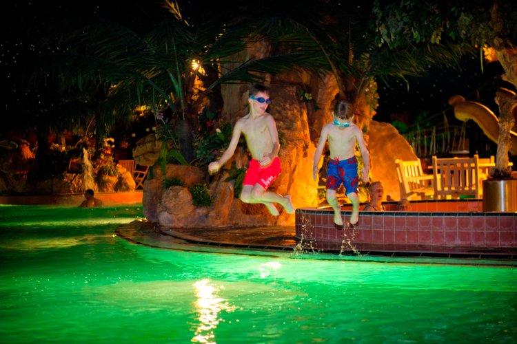 Jongens_springen_in_water_subtropisch_zwemparadijs
