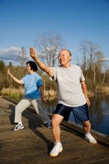 Мъж и жена тренират тай чи на вън
