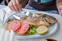 риба на грил с домат и жълт лимон в бяла чиния
